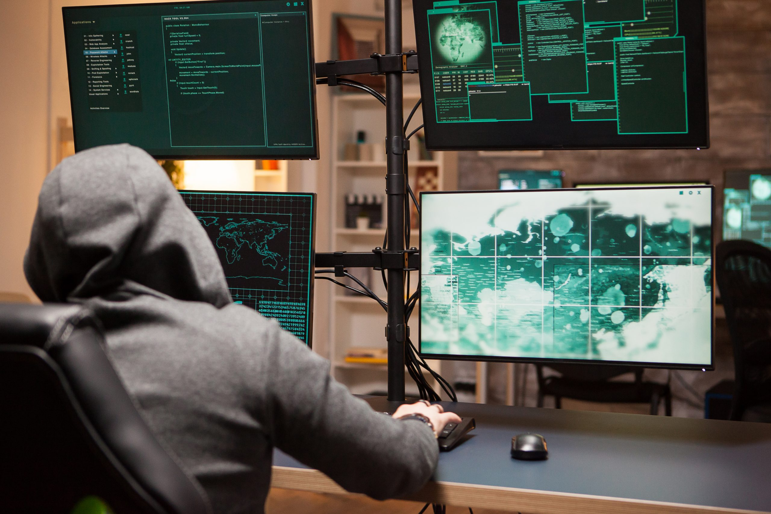 Cyber criminal wearing a hoodie writing a dangerous virus using computer with multiple screens.