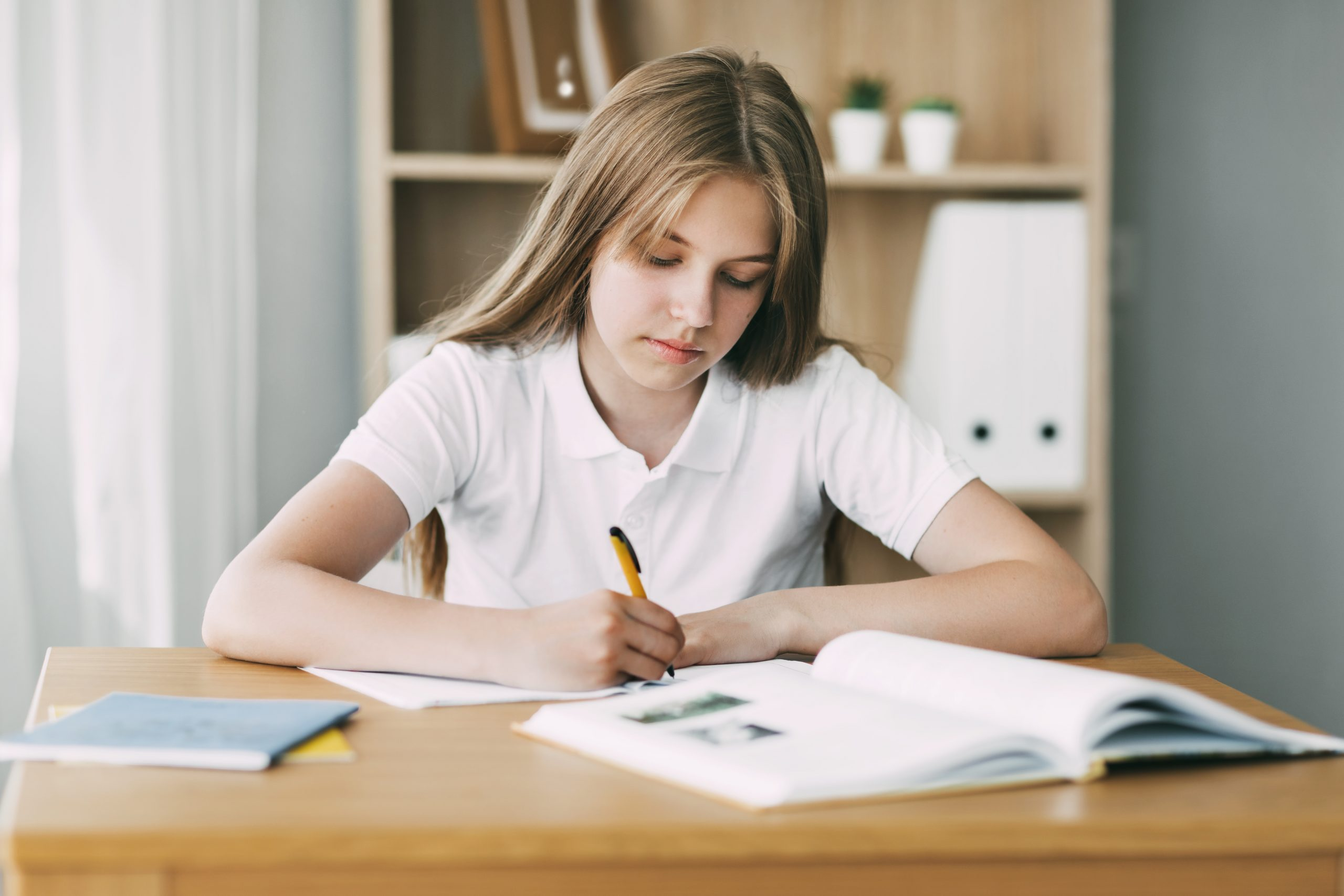 A high school student takes notes from a book, a teenage girl does her homework and prepares for lessons. Education, training, homework.