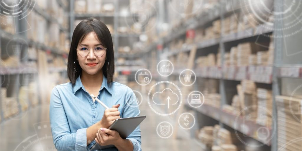 Portrait of happy young attractive asian entrepreneur woman looking at camera using smart tablet in warehouse with inventory management or industry digital era concept. Asian small business or sme.