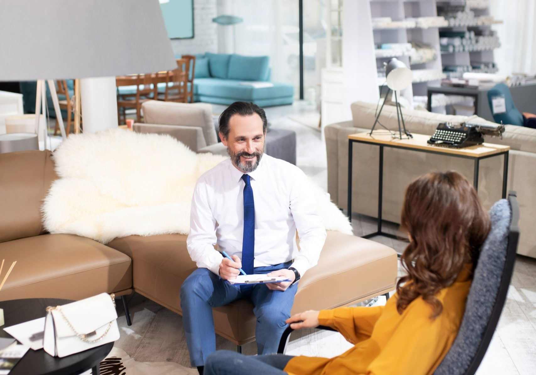 Cosy armchair. Consultant in tie and white shirt explaining advantages of new model